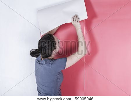 Woman hanging wallpaper.