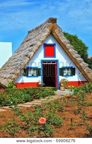 Charming rural house. The house with a thatched roof and gable front garden with rose bushes