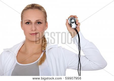 Blond girl in sportswear showing stopwatch