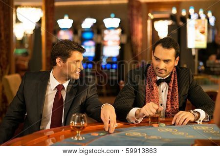 Two young men in suits behind gambling table in a casino