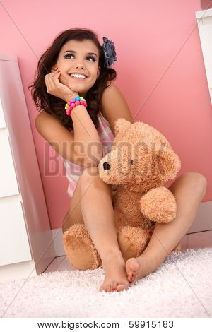 Happy teenage girl sitting on floor at home with teddy bear, smiling, daydreaming.
