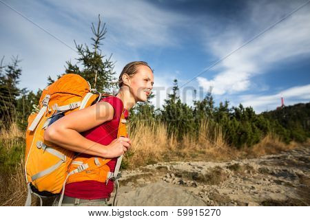 Pretty, female hiker going uphill in warm evening light