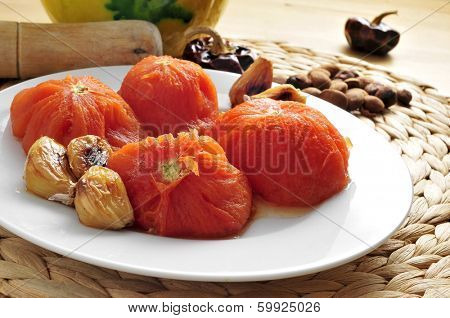 some ingredients to prepare romesco sauce typical of Catalonia, Spain, such as grilled tomatoes and garlics, toasted almonds or nyora pepper