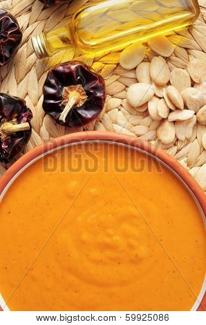 a bowl with romesco sauce, typical of Catalonia, Spain, with some of the ingredients to prepare it, such as nyora pepper, almonds and olive oil