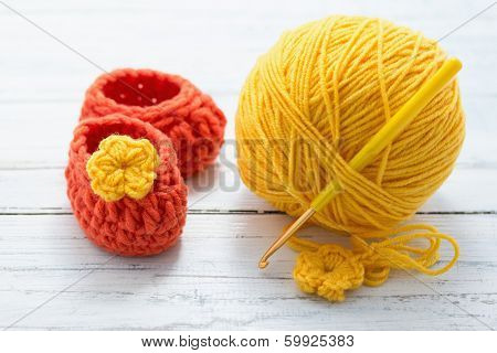 Yellow yarn and crocheted baby shoes