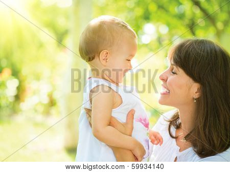 Beautiful Mother And Baby outdoors. Nature. Beauty Mum and her Child playing in Park together. Spring Outdoor Portrait of happy family. Joy. Mom and Baby