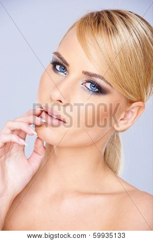 Beautiful dreamy young blond woman with downcast eyes wearing modern eye makeup  closeup face portrait on blue-grey