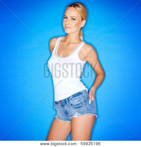 Cute blond woman in trendy frayed denim shorts on a blue background