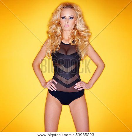 Seductive slender young blond woman in a sexy leotard standing against an yellow studio background