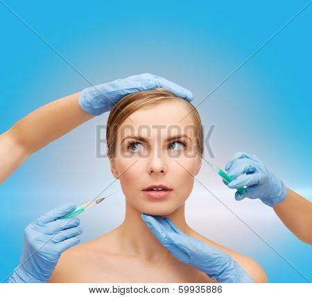 healthcare, beauty and medicine concept - beautiful scared woman face with closed eyes and beautician hands with syringe