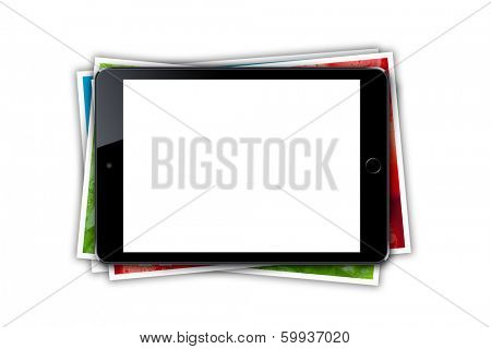 Tablet with blank screen and stack of printed pictures collage. Isolated on white background