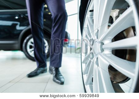 Seller or car salesman in car dealership presenting the extra decorations like sport rims of his new and used cars in the showroom
