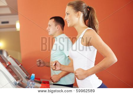 Young energetic girl training on treadmill