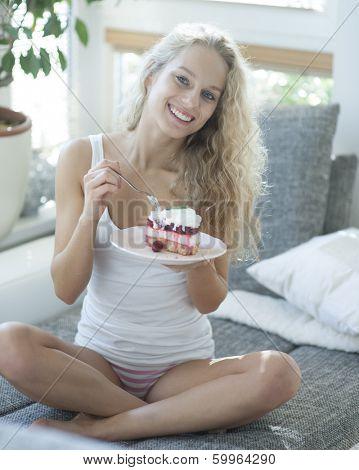 Full length portrait of woman having raspberry cake on sofa