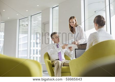 Business people working in office lobby