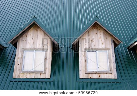 Two Dormer With Windows On The Green Roof