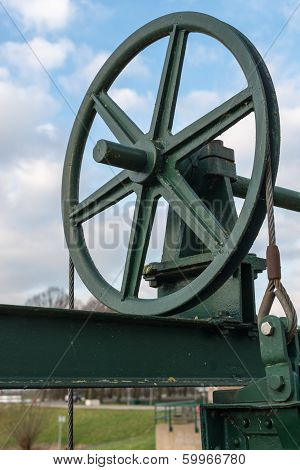 Historic Cast Iron Lifting Wheel Against The Blue Sky