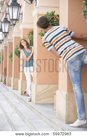Tourist couple playing hide-and-seek amongst columns