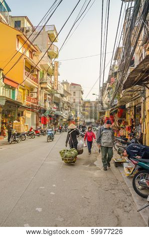 HANOI, VIETNAM, JANUARY 13, 2013 - busy street in Old Quarter, with small stores, street sellers and tourists