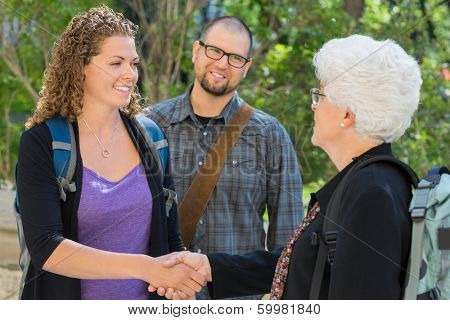 Female university students shaking hands at university campus with professor