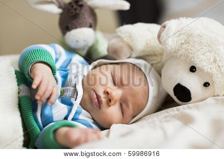 Resting time: Sweet peaceful baby boy sleeping during day time surrounded by toys.