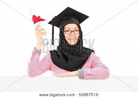 Female Islamic student with mortarboard and veil holding diploma behind blank panel isolated on white background