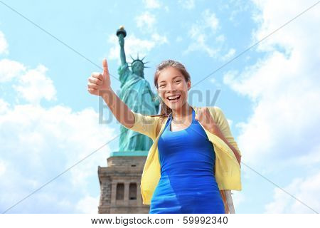 New York City Statue of Liberty Tourist woman giving thumbs up. Happy girl on tourism travel on Liberty Island, USA. Young multiethnic woman traveling having fun. Asian Caucasian woman.