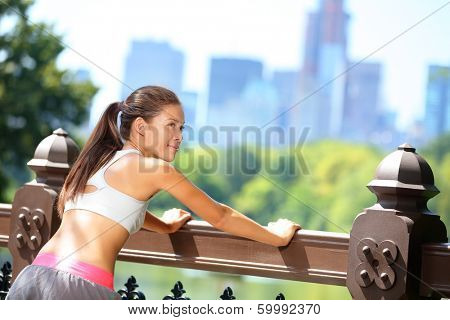 Running woman stretching after jogging in New York City, Central Park, Manhattan. Fit runner fitness sport model wearing sports bra. Female fitness jogger training outside for healthy lifestyle.