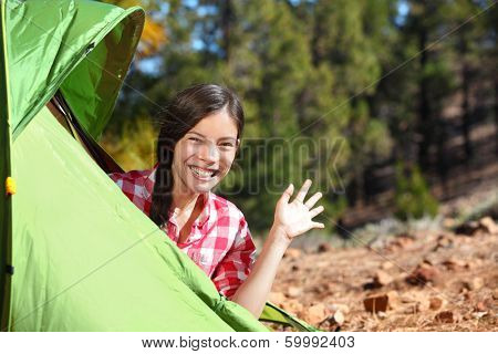 Camping woman waving hello from tent smiling happy outdoors in forest. Happy mixed race Asian Caucasian girl saying hi looking at camera.