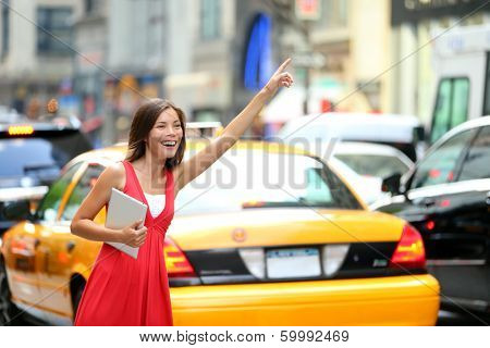 Girl calling taxi cab in New York City, holding tablet pc computer standing in cute summer dress in street of Manhattan, USA. Beautiful young mixed race Asian Caucasian woman outdoor.