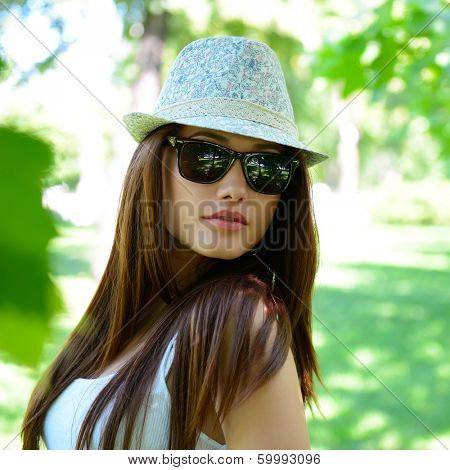 young beautiful lady outdoor portrait, girl in summer park  in sunglasses and fedora with long brown hair