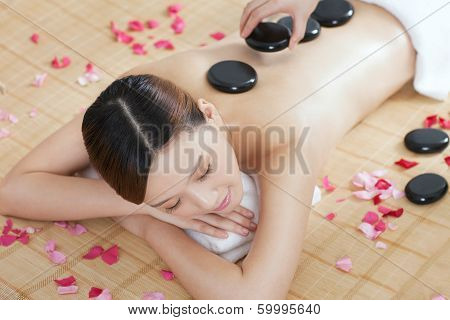 .a Young Lady Enjoying Stone Massage At Spa.