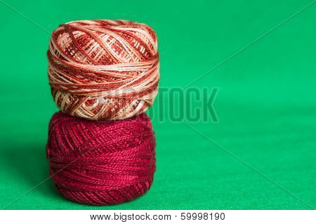 Red And Melange Balls Of A Yarn On A Green Background