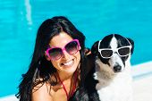 image of dog eye  - Happy woman and dog on funny summer vacation portrait wearing sunglasses at poolside - JPG