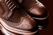 foto of welts  - Unworn laced pair of two tone men brogues (derbys) with elegant toe shape. The upper is stunning combination of brown calf with brown suede. Isolated on dark brown background with mirror reflection.