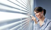 stock photo of peek  - Young attractive woman smiling and peeking through blinds at window - JPG