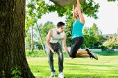 Young woman and personal trainer exercising chins or pull ups in City Park under summer trees for sp