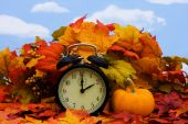 stock photo of daylight saving time  - Fall coloured leaves with a black clock on a sky background Fall Leaves - JPG