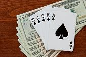 picture of twenty dollar bill  - Spade royal flush sits on top of a stack of twenty dollar bills - JPG