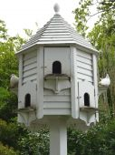 stock photo of pigeon loft  - White wooden dove cot for pigeons with small arched doorways - JPG