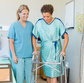 Full length of mid adult female patient walking with the help of walker while nurse looking at her i