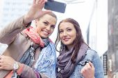 stock photo of two women taking cell phone  - Women in jackets taking self portrait through mobile phone - JPG