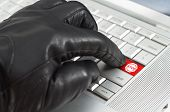 Hacker Concept With Hand Wearing Black Leather Glove Pressing Enter Key Button On A Metallic Laptop