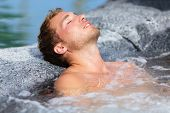 Wellness Spa - man relaxing in hot tub whirlpool Jacuzzi outdoor at luxury resort spa retreat. Hands