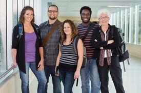 foto of professor  - Group portrait of confident multiethnic university students standing in corridor with professor - JPG