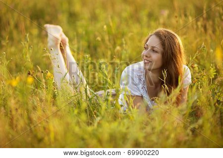 Happy Woman Lying In A Field Of Grass And Flowers