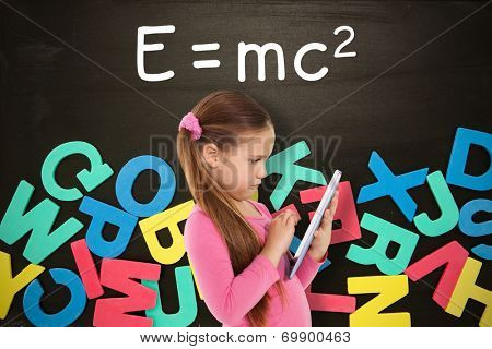Cute girl using tablet against alphabet magnets in a jumble on blackboard