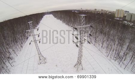 Big power line in the snowy forest near the city, aerial view