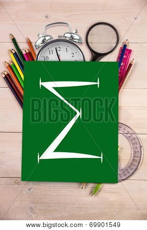 Sum symbol against students desk with green page