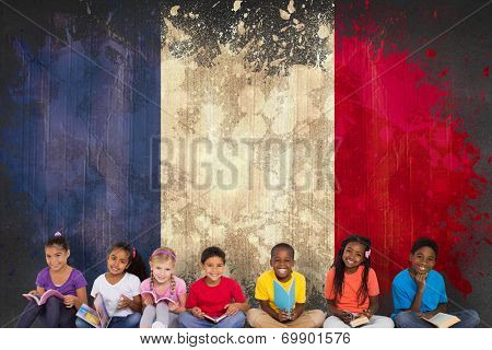 Elementary pupils reading books against france flag in grunge effect